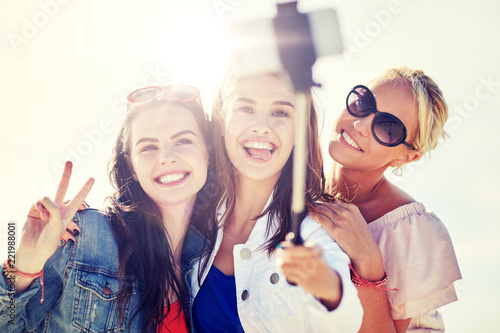 summer vacation, holidays, travel, technology and people concept- group of smiling young women taking picture with smartphone on selfie stick on beach - 221988001