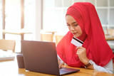 Portrait of attractive female Arabic holding credit card and using laptop for shopping or payment online. - 221988478