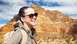 adventure, travel, tourism, hike and people concept - smiling young woman with backpack over grand canyon national park background - 221991431