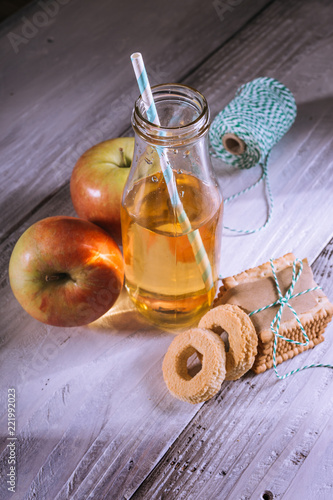 Fototapeta apple juice in bottle and biscuits on white wooden table