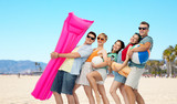 leisure and summer holidays concept - group of happy smiling friends in sunglasses with ball, volleyball, towel, camera and air mattress over venice beach background
