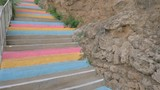 Steadicam pov shot of walking up the outdoor staircase with pink, orange and blue stairs - 221993260