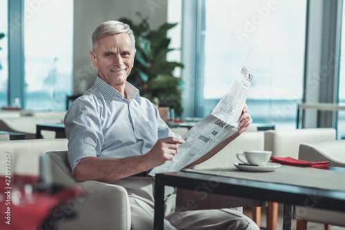 Leinwanddruck Bild Have a look. Handsome male person holding newspaper in both hands while being in cafe