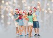 christmas, holidays and friendship concept - group of happy smiling friends in santa hats having fun over festive lights background