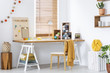 Yellow blanket on chair at wooden desk with lamp and colorful yarns in modern interior. Real photo