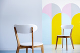 Two white chairs facing each other in a bright office interior with pastel decorations. Real photo with blurred foreground - 221993838