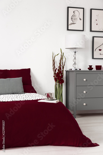 Real photo of a romantic bedroom interior with dark red sheets on a bed, flower and grey commode. Empty wall, place your poster