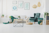 Green accents, graphics and modern coffee table in a living room interior. Real photo - 221994003