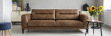 Brown leather sofa in real photo of bright living room interior with fresh flowers, decor and books on cupboard - 221994014