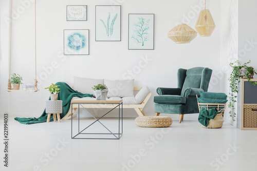 Foto Murales Green accents, graphics and modern coffee table in a living room interior. Real photo