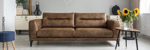 Brązowy skórzana sofa w prawdziwym zdjęcie jasny salon wnętrza ze świeżych kwiatów, wystrój i książek na szafce
