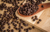 Full of coffee beans in wooden spoon on burlap background - 221994237