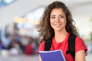 Portrait of a cute young student girl holding colorful notebook