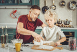 Some flour. Dark-haired father adding some flour to dough for future pie while son rolling out pastry - 221997016