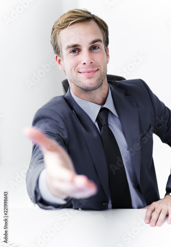 Smiling businessman giving hand for handshake - 221998643