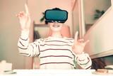 Virtual reality. Pleasant smiling woman having fun wearing VR glasses - 222000655