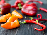 different types of peppers on a wooden table - 222005456