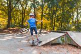 Ein Mädchen skatet mit dem Longboard auf einem Skatepark eine Rampe hinauf