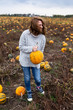Woman with a pumpkin on a pumpkin field