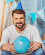 Time for childhood. Optimistic appealing man grinning while holding balloon