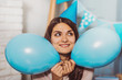 In anticipation. Nice energetic woman holding balloons while looking aside