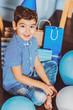Birthday present. Cheerful gay boy staring at camera while posing among gifts