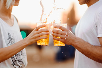Couple cheering with beer. Close up