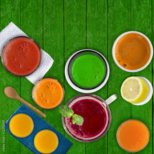 Fototapeta Set of different vegetable juices and fruit drinks, mint leaf and lemon on rustic green wooden table. Concept of healthy eating and drinks. Top view. Copy space.