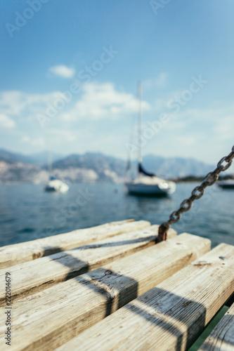 Bootsanlegestelle: Holzsteg, blaues Wasser, Kette und Boote, Unschärfe