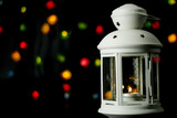Christmas white lantern with a burning candle on the background of colorful lights garland, bokeh. - 222015089
