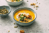 Pumpkin soup in a bowl with croutons and pumpkin seeds. Autumn food. - 222017427