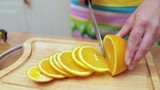 Women's hands Housewives cut with a knife fresh orange on the cutting Board of the kitchen table - 222020646