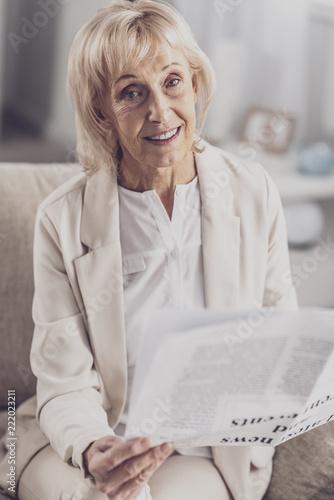 Beżowy kostium. Piękne przyjemny wygląd starsza kobieta ubrana w stylowy beżowy strój siedzi w salonie