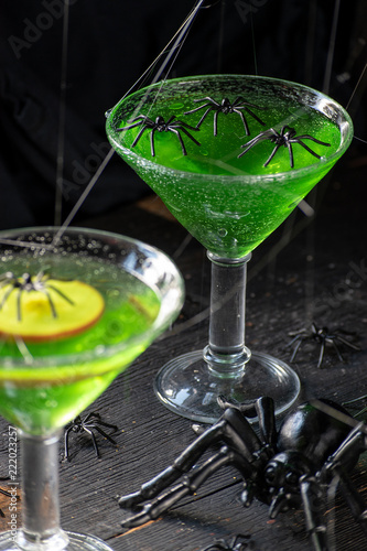 Fototapeta Halloween bright green dessert topped with apple slice with black spiders and spider webs
