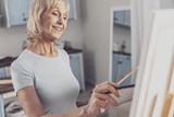 Joyful hobby. Elderly smiling woman wearing plain white shirt enjoying her hobby while standing in the kitchen - 222024893
