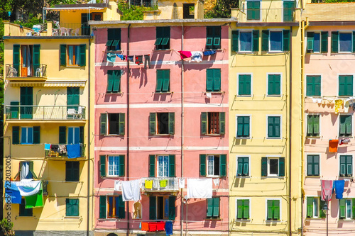 View on the beautiful colourful houses with clothes drying in the sunny daylight in Cique Terre, Italy.