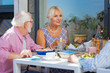 Pleasurable time. Pleasant aged woman looking at her friend while eating lunch with them