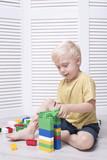 Little blond boy is building of colored designer - 222034461