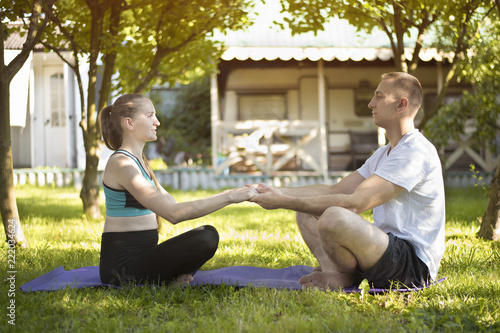 Poster Pair of lovers sit on a rug for yoga and hold hands. Morning in the summer garden