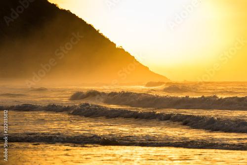 Wschód słońca na plaży z wybrzeżem górskim