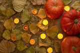 Pumpkins with candles on leaves. Autumn texture, concept of Halloween - 222036243