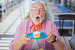 Birthday party. Delighted senior man holding a plate with cake while celebrating his birthday
