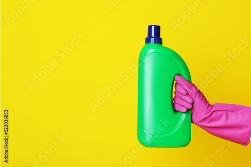 Leinwandbild Motiv Female hand holding bottle with detergent on yellow background