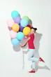 Beautiful young girl with colored balloons on white background