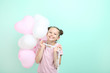 Leinwanddruck Bild - Beautiful young girl with balloons on mint background