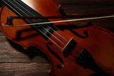 Violin with bow on brown wooden table - 222037239