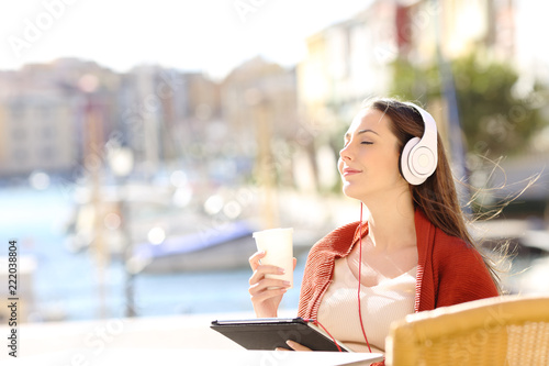 Poster Girl relaxing in a coffee shop listening to music on vacation