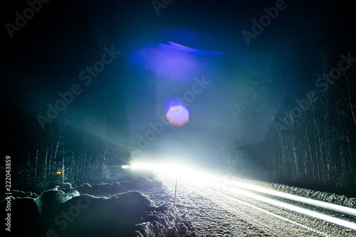 Fototapeta Car headlights on a winter road in the forest, on long exposure