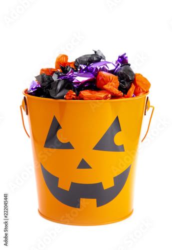 Leinwanddruck Bild Pumpkin Bucket Filled with Various Wrapped Candies