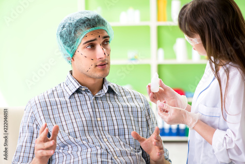 Leinwandbild Motiv Plastic surgeon preparing for operation on man face
